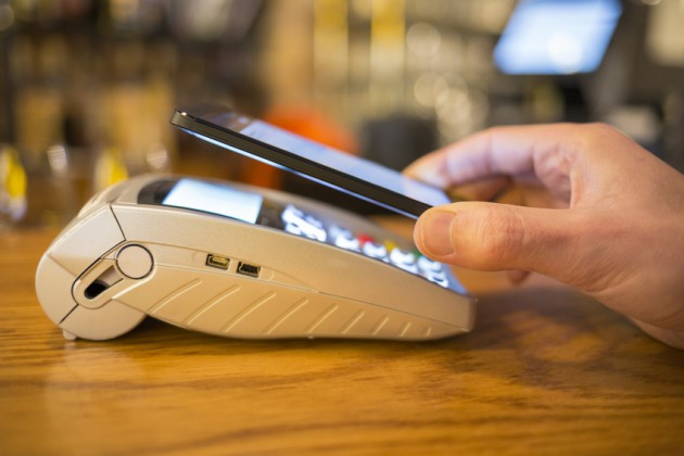 Man paying with NFC technology on mobile phone, restaurant, shop